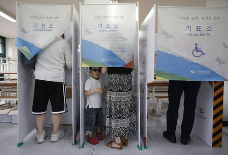 A boy waits for his mother as she marks her ballot in a voting booth for the local elections at a polling station in Seoul June 4, 2014. REUTERS/Kim Hong-Ji