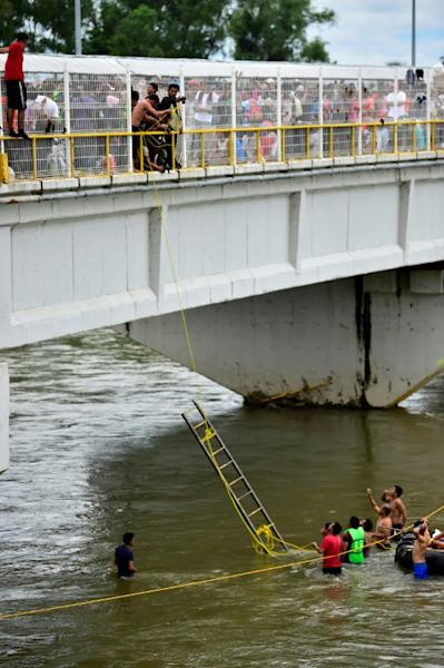 Honduran migrants, heading in a caravan to the US, help others get down to the Suchiate River from the Guatemala-Mexico international border bridge, in Ciudad Hidalgo, Chiapas state, Mexico