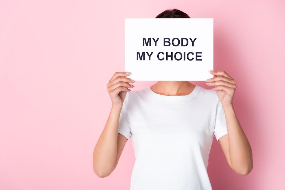 woman in white t-shirt holding placard with my body my choice lettering while covering face on pink