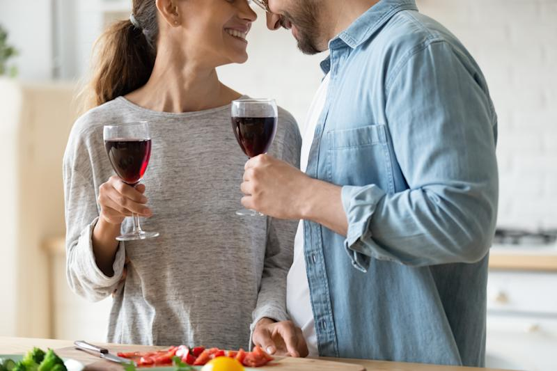 Close up happy loving couple holding glasses, drinking red wine, smiling young woman and man touching foreheads, enjoying romantic date, standing in kitchen, celebrating relocation or anniversary