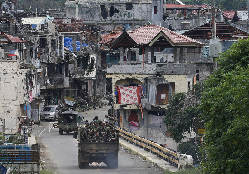 FILE - In this Oct. 19, 2017, file photo, Philippine troops head back to the devastated village of Mapandi which has been cleared of Islamic State group-linked militants in Marawi city in southern Philippines. President Donald Trump contended this week that the United States saved the Philippines from Islamic State terrorism. His assertion overstated both the threat IS posed to the country and what the U.S. did about it.. (AP Photo/Bullit Marquez, File)