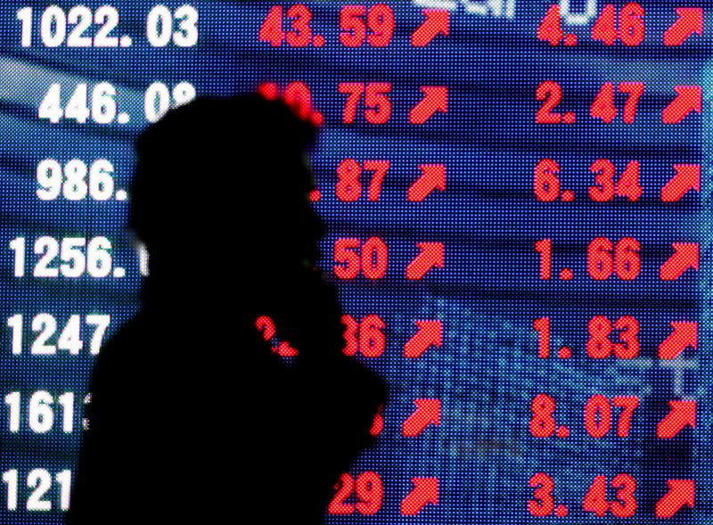 FILE PHOTO: Man is silhouetted against stock quotation board in Tokyo