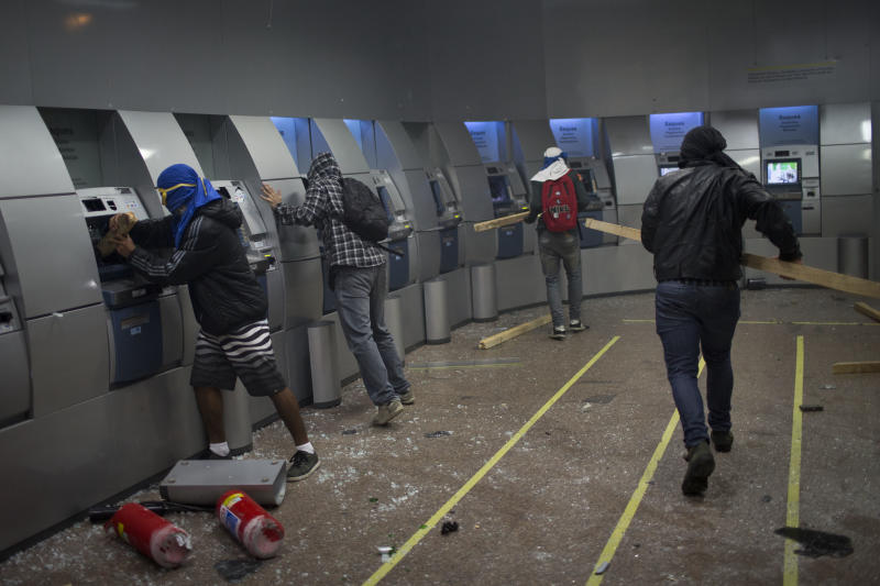 FILE - In this Oct. 7, 2013 file photo, Black Bloc anarchists break ATM machines inside a bank after a march in support of teachers on strike in Rio de Janeiro, Brazil. The Black Bloc, a violent form of protest and vandalism that emerged in the 1980s in West Germany, has become a driving force in Brazil behind protests in recent weeks. The young Brazilians are following the main anti-capitalist tenets of earlier versions, smashing scores of banks and multinational businesses during demonstrations and directly confronting riot police. (AP Photo/Felipe Dana, File)