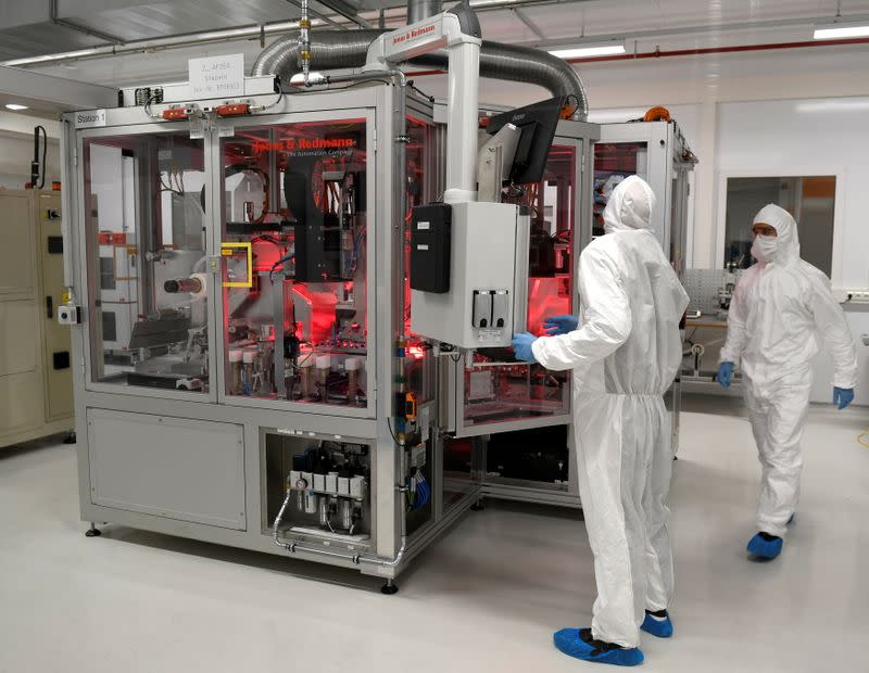 FILE PHOTO: Employees of German carmaker Volkswagen work in a production line of VW' new battery plant in Salzgitter