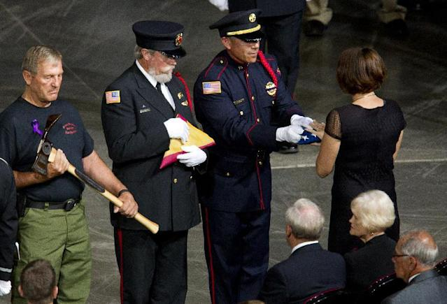 A flag is presented to Juliann Ashcraft, widow of fallen firefighter Andrew Ashcraft, during a memorial service for the 19 fallen firefighters at Tim's Toyota Center in Prescott Valley, Ariz. on Tuesday, July 9, 2013. Prescott's Granite Mountain Hotshots were overrun by smoke and fire while battling a blaze on a ridge in Yarnell, about 80 miles northwest of Phoenix on June 30, 2013. (AP Photo/The Arizona Republic, Michael Chow, Pool)