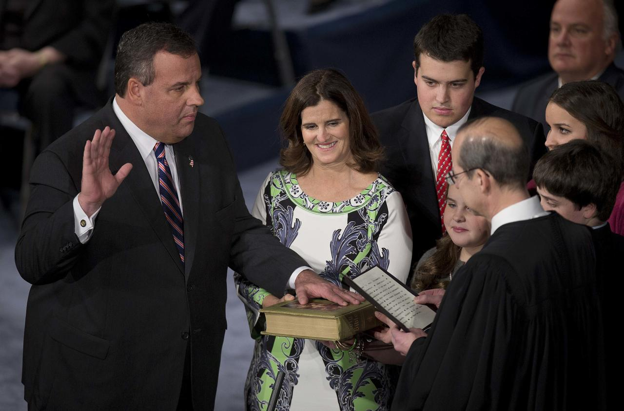 Governor Chris Christie holds his hand aloft as he is sworn in for his second term at the War Memorial Theatre in Trenton, New Jersey January 21, 2014. Christie, a Republican Party star enmeshed in scandal after re-election in November, will return to the themes of small government and bipartisan cooperation when he is sworn in for a second term on Tuesday. REUTERS/Carlo Allegri (UNITED STATES - Tags: POLITICS)