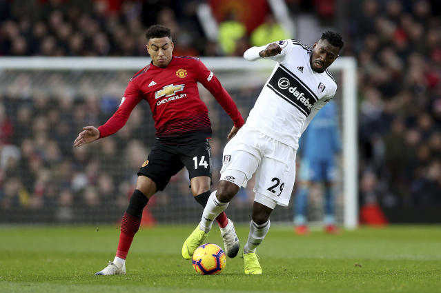 Manchester United's Jesse Lingard, left, and Fulham's Andre-Frank Zambo Anguissa in action during their English Premier League soccer match at Old Trafford, Manchester, England, Saturday, Dec. 8, 2018. (Barrington Coombs/PA via AP)
