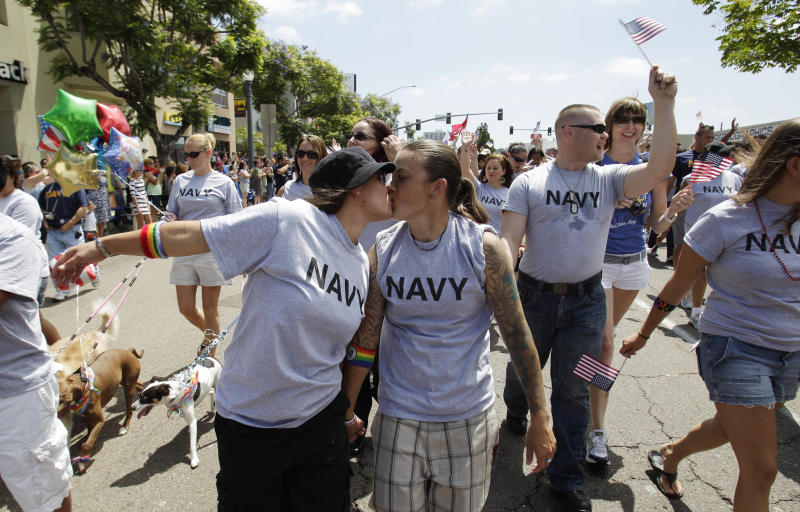 FILE - In this July 16, 2011 file photo, two women, both active duty sailors in the Navy who gave their names as Nikki, left, and Lisa, kiss as they march in the Gay Pride Parade in San Diego. The Defense Department on Thursday, July 19, 2012 announced it is allowing service members to march in uniform in a gay pride parade for the first time in U.S. history. The department said it was making the exception for Saturday's San Diego Gay Pride Parade because organizers had encouraged military personnel to march in their uniform and the event was getting national attention. (AP Photo/Gregory Bull, File)