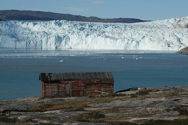 The original hut built by a French exploration team led by Paul-Emile Victor in 1948 stands opposite the Eqip Sermia Glacier, also called the Eqi Glacier, during unseasonably warm weather at Eqip Sermia, Greenland. (Photo: Sean Gallup/Getty Images)