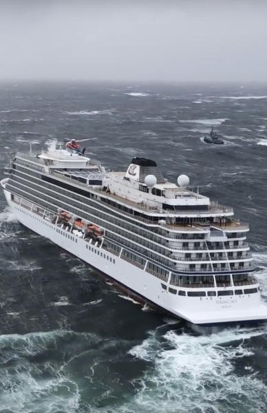 In this image taken from video made available by CHC helicopters, helicopters fly over the cruise ship Viking Sky after it sent out a Mayday signal because of engine failure in windy conditions off the west coast of Norway, Saturday March 23, 2019. A cruise ship with engine problems sent a mayday call off Norway's western coast on Saturday, then began evacuating its 1,300 passengers and crew amid stormy seas and heavy winds in a high-risk helicopter rescue operation. (CHC helicopters via AP)
