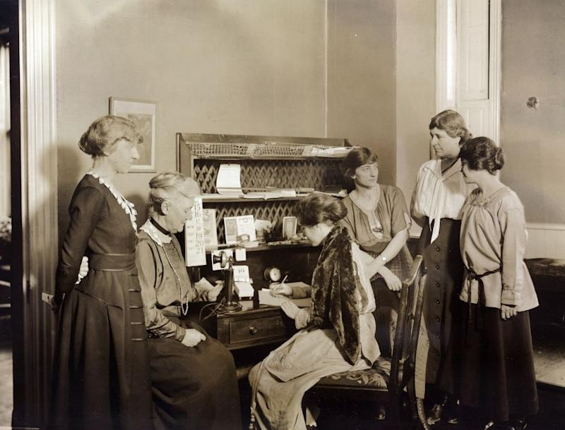Six National Woman's Party members gathered around a desk at National Woman's Party headquarters. Left to right: Mabel Vernon, Dora Lewis, Alice Paul (seated), Florence Brewer Boeckel, Abby Scott Baker, and Anita Pollitzer. Feb. 1921.   Photo 12—Universal Images Group via Getty