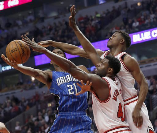 Chicago Bulls' Nazr Mohammed, front, and Jimmy Butler defend Orlando Magic's Maurice Harkless during the first half of an NBA basketball game Friday, April 5, 2013, in Chicago. (AP Photo/Charles Cherney)