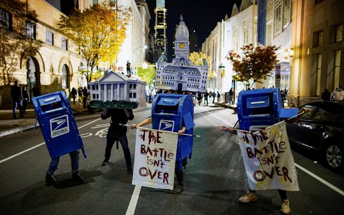 Activists dressed as the White House, Philadelphia City Hall and the United States Postal Service mailboxes stand on a street in Philadelphia - REUTERS