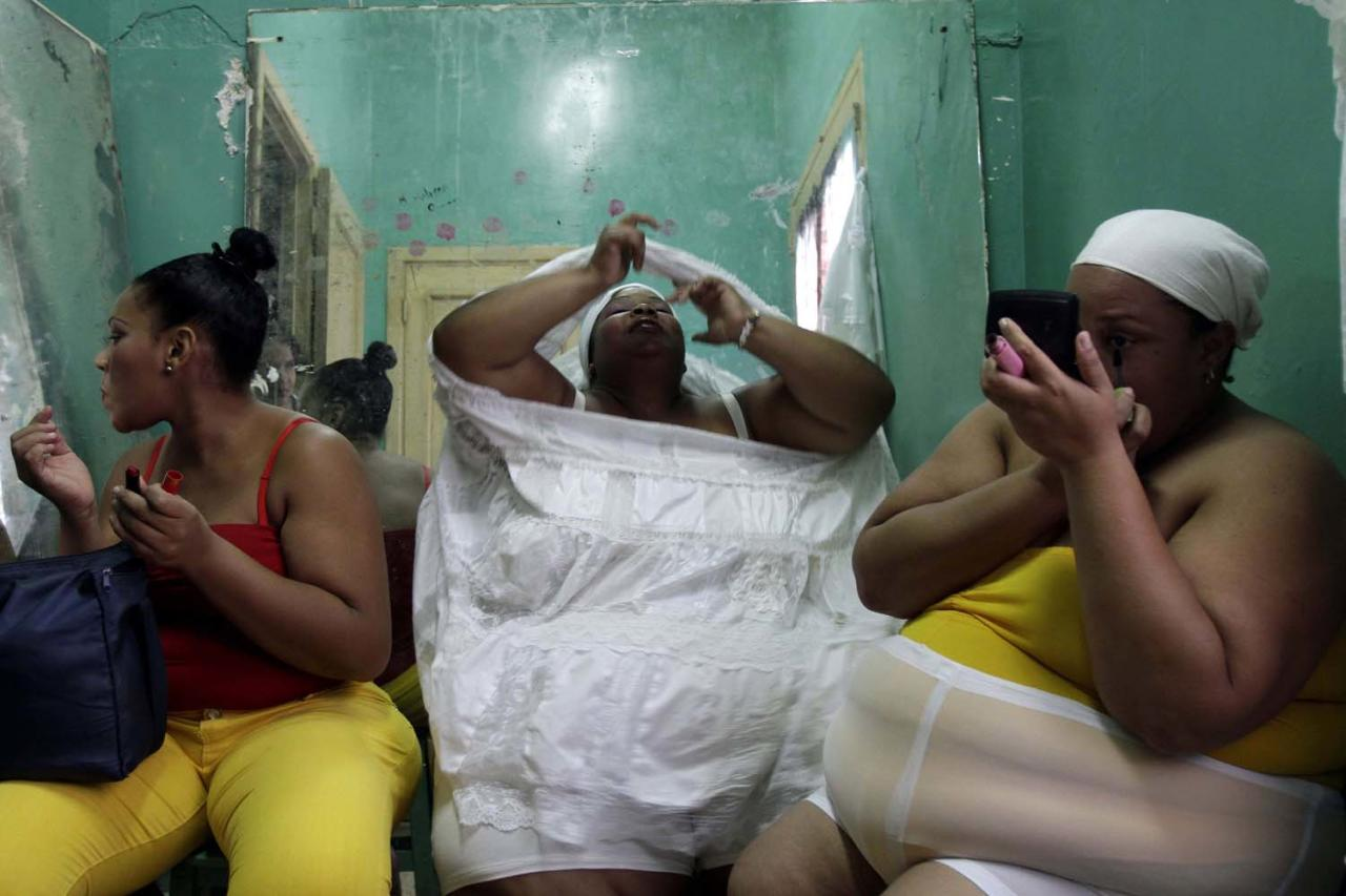 Dancers Maylin Daza, right, Barbara Paula, center and Rubi Amaro get dress and apply make up before dancing with their group Danza Voluminosa or Voluminous Dance in Havana, Cuba, Saturday, Nov. 24, 2012. Voluminous Dance is a theater company with overweight dancers founded by dancer, choreographer and director Juan Miguel Mas. (AP Photo/Franklin Reyes)