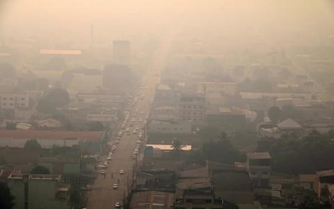 A general view over smoke from fires in teh Amazon rainforest that cover the city of Porto Velho - Credit: Rex