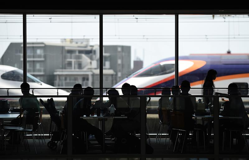 Visitors enjoy lunch as bullet trains pass the restaurant of the railway museum in Omiya, Saitama prefecture, on August 1, 2014 (AFP Photo/Toshifumi Kitamura)