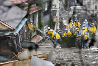 Rescuers conduct a search operation inside a building at the site of a mudslide at Izusan in Atami, Shizuoka prefecture, southwest of Tokyo, Sunday, July 4, 2021. More than 1,000 soldiers, firefighters and police on Sunday waded through a giant mudslide that ripped through the resort town as it swept away houses and cars. (Kyodo News via AP)
