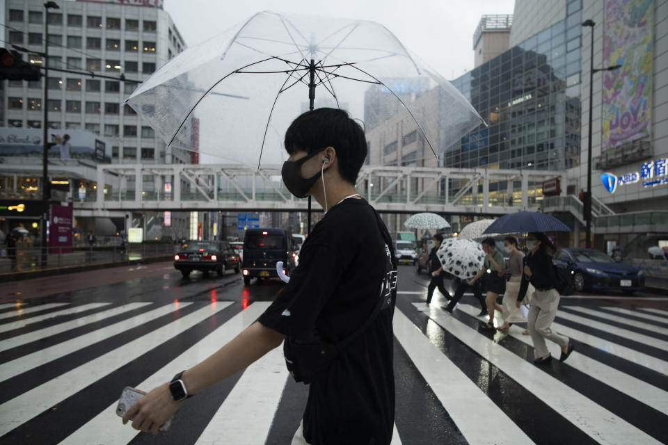 A man wearing a face mask to help curb the spread of the coronavirus walks across an intersection in a drizzle in Tokyo, Thursday, Sept. 2, 2021. (AP Photo/Hiro Komae)