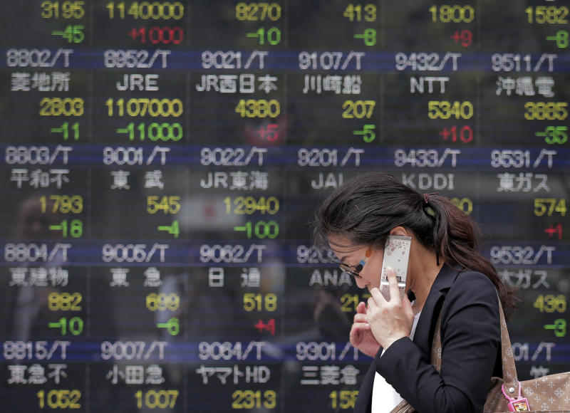 A woman walks by an electronic stock board of a securities firm in Tokyo, Wednesday, July 24, 2013. Asian stock markets were mostly lower Wednesday after a survey showed Chinese manufacturing activity fell to its lowest point in nearly a year. Japan's Nikkei 225 fell 0.6 percent to 14,692.83. (AP Photo/Itsuo Inouye)