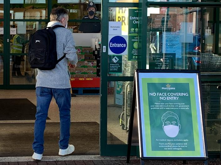 A sign at the entrance informs customers that they must wear a face mask because of the coronavirus pandemic at a Morrisons supermarket in Ellesmere Port, northwest EnglandAFP via Getty Images