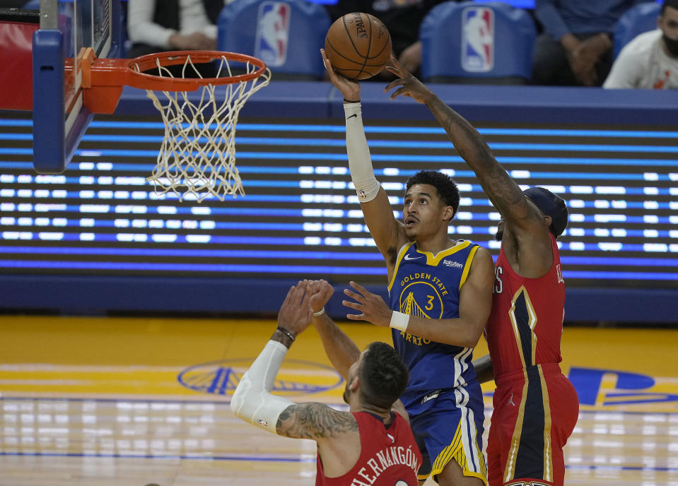 Golden State Warriors guard Jordan Poole (3) shoots against New Orleans Pelicans guard Eric Bledsoe, right, and center Willy Hernangomez, bottom, during the first half of an NBA basketball game on Friday, May 14, 2021, in San Francisco. (AP Photo/Tony Avelar)