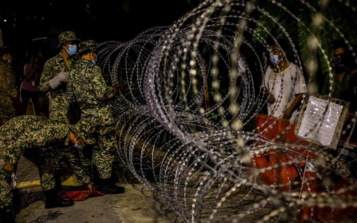 Security forces set up barbed wire in Kampung Segambut on Saturday as the National Security Council ordered a total lockdown for two weeks after the increase in Covid cases in several districts in Kuala Lumpur - Syaiful Redzuan/Anadolu Agency