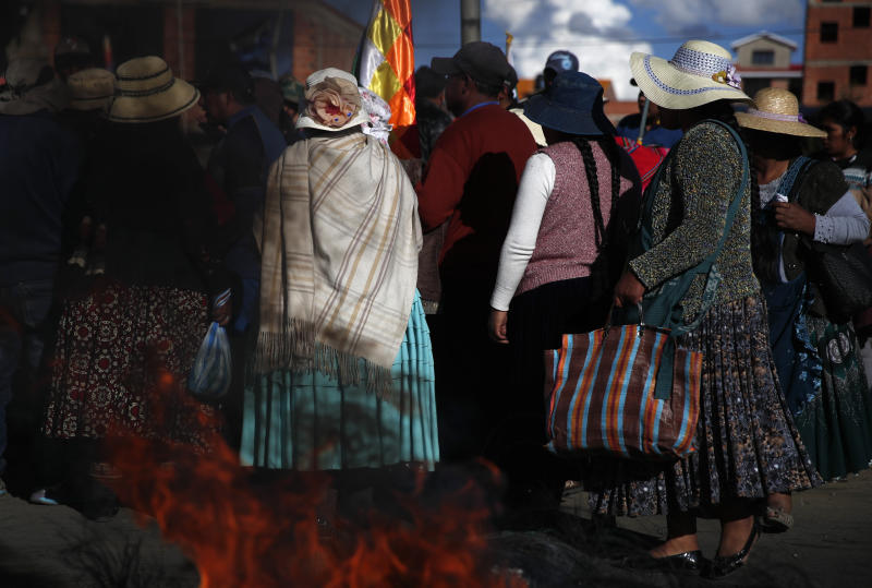 Supporters of former President Evo Morales stand next to a burning tire at a blockade along a road leading to the state-own Senkata gas filing plant in El Alto, Bolivia, Sunday, Nov. 17, 2019. (AP Photo/Natacha Pisarenko)