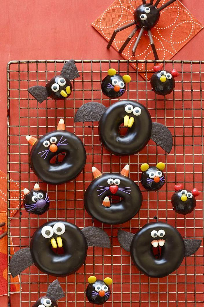 """<p>The kids will love creating these creepy critter treats. Just hand them some candy corn and M&Ms and let them get creative. </p><p><em><strong><a href=""""https://www.womansday.com/food-recipes/food-drinks/a23460042/black-cat-bat-spider-and-mice-doughnuts-recipe/"""" rel=""""nofollow noopener"""" target=""""_blank"""" data-ylk=""""slk:Get the Black Cat, Spider, and Mice Doughnuts recipe."""" class=""""link rapid-noclick-resp"""">Get the Black Cat, Spider, and Mice Doughnuts recipe.</a></strong></em></p>"""