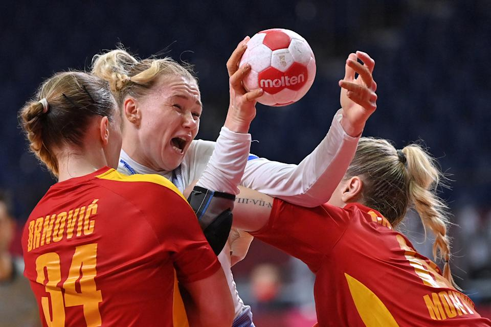 <p>Russia's pivot Kseniia Makeeva (C) is challenged during the women's quarterfinal handball match between Montenegro and Russia of the Tokyo 2020 Olympic Games at the Yoyogi National Stadium in Tokyo on August 4, 2021. (Photo by Fabrice COFFRINI / AFP)</p>