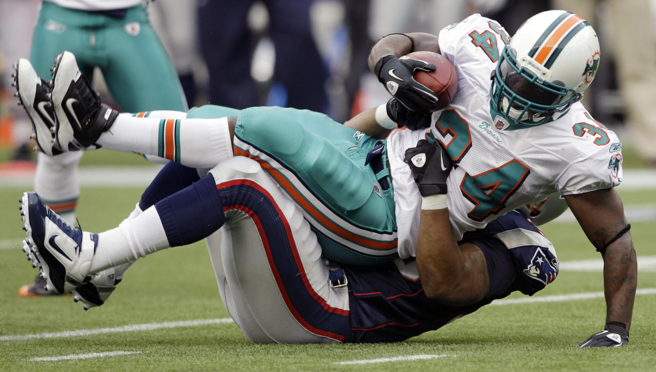 Miami Dolphins running back Ricky Williams (34) is brought down by New England Patriots defensive lineman Eric Moore (98) during the first quarter of their NFL football game in Foxborough, Mass., Sunday afternoon, Jan. 2, 2011.