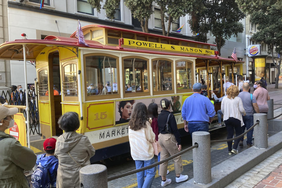 People line up to board a cable car at the Powell Street turnaround plaza in San Francisco on Monday, Aug. 2, 2021. San Francisco's iconic cable cars are rolling again after being sidelined by the pandemic for months. People were already forming long lines to ride the cable cars, which will offer free rides the month of August. (AP Photo/Olga Rodriguez)