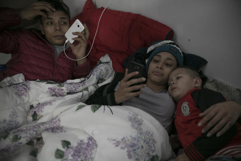 FILE - In this Feb. 8, 2019 file photo, 17-year-old Honduran migrant Josue Mejia Lucero, his girlfriend Milagro de Jesus Henriquez Ayala, 15, and Josue's 3-year-old nephew Jefferson, look at cell phones as they lie in bed at the Agape World Mission shelter in Tijuana, Mexico. Hundreds of Central Americans are now getting as many details as possible before leaving north towards the U.S. border. Increasingly they're organized over Facebook and WhatsApp as they try to join together in large groups they hope will make the trip safer, and without having to hide themselves from authorities. (AP Photo/Emilio Espejel, File)