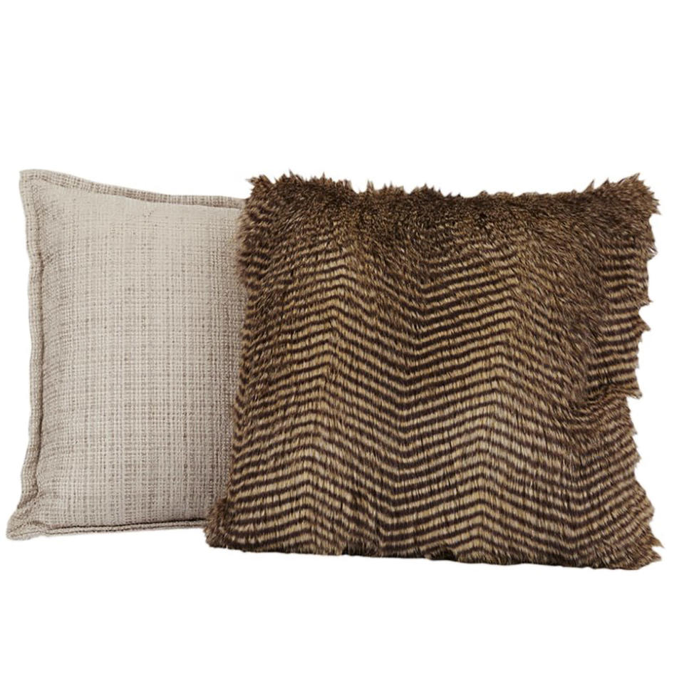 This image provided by HomeGoods shows faux fur pillows. Marcy Blum, a NY-based wedding and event planner suggests filling a basket with throws and pillows for guests who will be gathering outdoors during your Noon Year's Eve bash. (HomeGoods via AP)