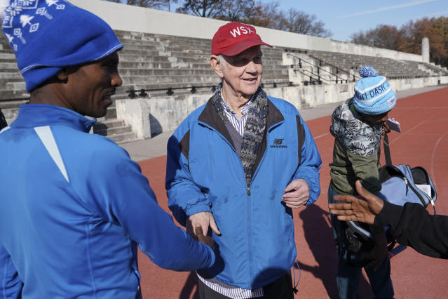 Runners say goodbye to Bill Staab, center, after a short workout at Van Cortlandt Park in the Bronx borough of New York, Tuesday, Nov. 26, 2019. Girma Bekele Gebre stunned the elite field at the New York City Marathon by finishing third as a nonelite entrant in November. It was a life-changing performance for the Ethiopian runner, and one made possible because of his involvement with the West Side Runners' Club. Staab, president of the team, has spent four decades helping immigrant runners acquire visas and gain entry to U.S. races, spending nearly $1 million of his own money to cover fees. Bekele Gebre is his greatest success, but not nearly the only runner he's helped. (AP Photo/Seth Wenig)