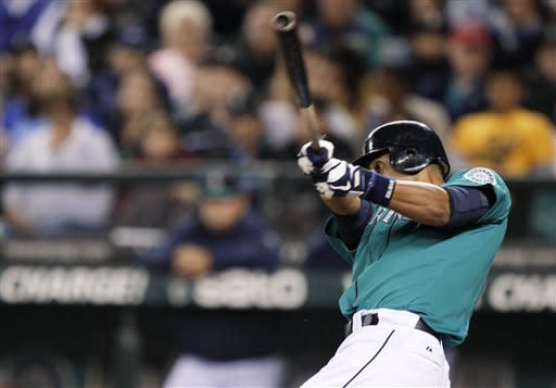 Seattle Mariners' Franklin Gutierrez hits into a play that allowed him to reach first base on an error by Texas Rangers third baseman Michael Young that also allowed Carlos Triunfel to score, in the fourth inning of a baseball game Friday, Sept. 21, 2012, in Seattle. (AP Photo/Ted S. Warren)