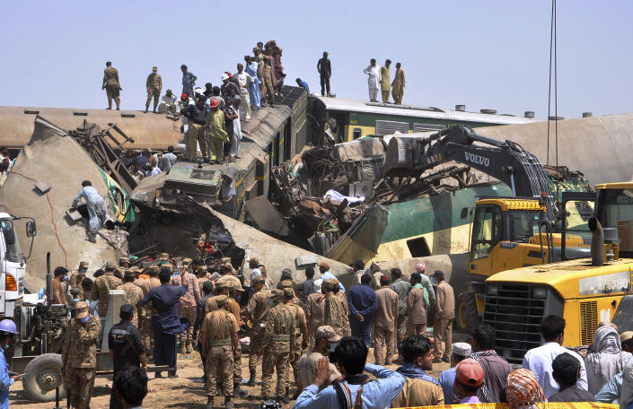 Soldiers and volunteers work at the site of a train collision in the Ghotki district in southern Pakistan, Monday, June 7, 2021. Two express trains collided in southern Pakistan early Monday, killing dozens of passengers, authorities said, as rescuers and villagers worked to pull injured people and more bodies from the wreckage. (AP Photo/Waleed Saddique)
