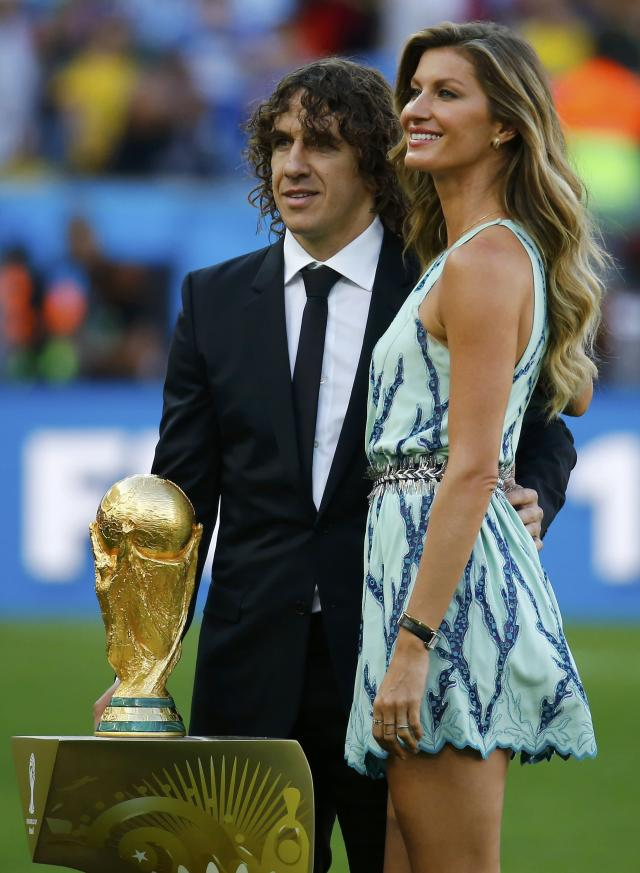 Retired footballer Carles Puyol of Spain (L), a member of the 2010 World Cup winning team, and Brazilian supermodel Gisele Bundchen pose with the World Cup trophy before the 2014 World Cup final between Germany and Argentina at the Maracana stadium in Rio de Janeiro July 13, 2014. REUTERS/Kai Pfaffenbach (BRAZIL - Tags: SOCCER SPORT WORLD CUP)