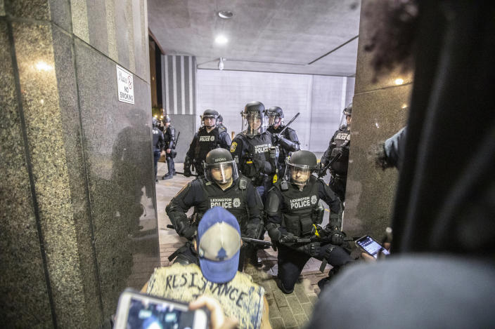 """Two police officers kneel after protesters attending a rally against the deaths of George Floyd and Breonna Taylor chanted """"Kneel with us! Kneel with us!"""" in Lexington, Ky., on Sunday, May 31, 2020. (Ryan C. Hermens/Lexington Herald-Leader via AP)"""