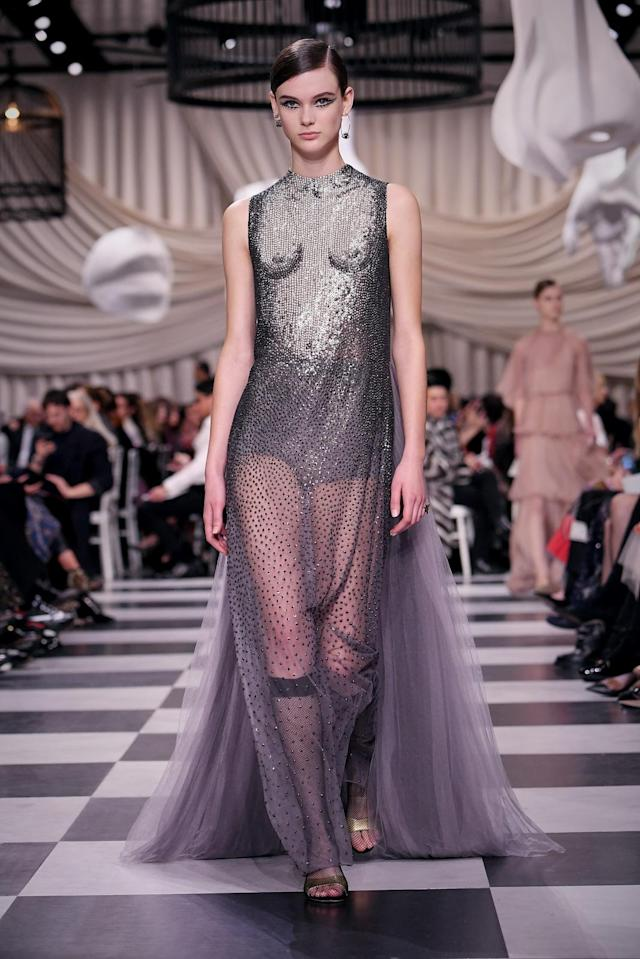 <p>A model wears a silver shimmery dress depicting a woman's unclothed torso and chest with a long sheer tulle bottom from the Dior Haute Couture SS18 collection. (Photo: Getty) </p>