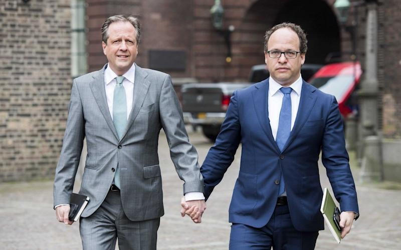 Alexander Pechtold, leader of the Democrats D66 party, and Wouter Koolmees, financial specialist of D66, hold hands as they arrive for talks in The Hague - Credit: EPA/LEX VAN LIESHOUT