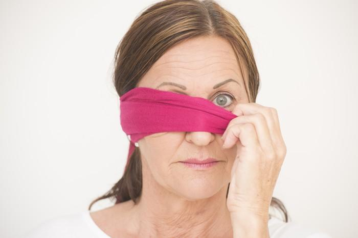 Mature woman removing a blindfold.
