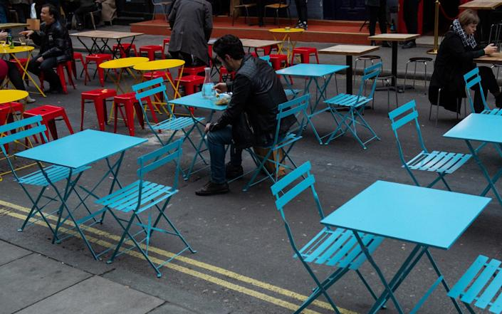 People eat outside restaurants in Soho, London, on the first day after the city was put into Tier 2 restrictions to curb the spread of coronavirus. - Dominic Lipinski/PA Wire