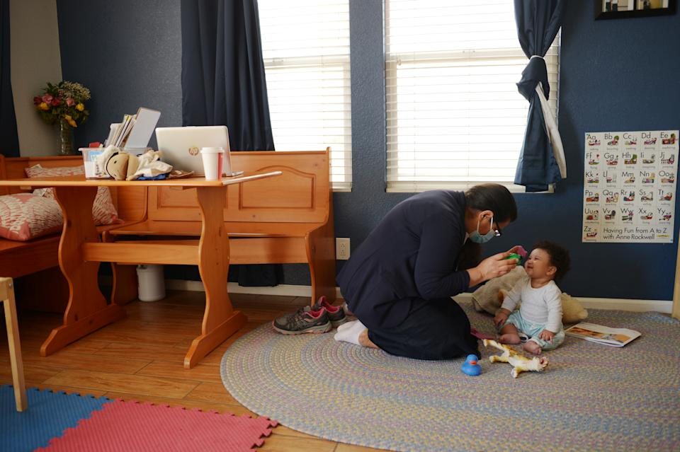 DENVER, CO - MARCH 3 : Flora Montes-Moreno, left, baby-sits 6 month old girl at Little Rascals child care center in Denver, Colorado on Wednesday, March 3, 2021. Flora Montes-Moreno, a child care provider whose business and life have been totally upended during the pandemic. She used to have 11 child care students and now she is down to one client she regularly works with. (Photo by Hyoung Chang/MediaNews Group/The Denver Post via Getty Images)