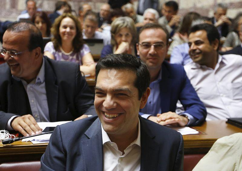 Greek Prime Minister Alexis Tsipras smiles before a ruling Syriza party parliamentary group session in Athens