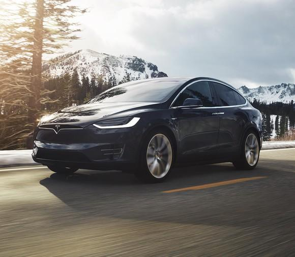 A black Tesla Model X driving on a mountain road.