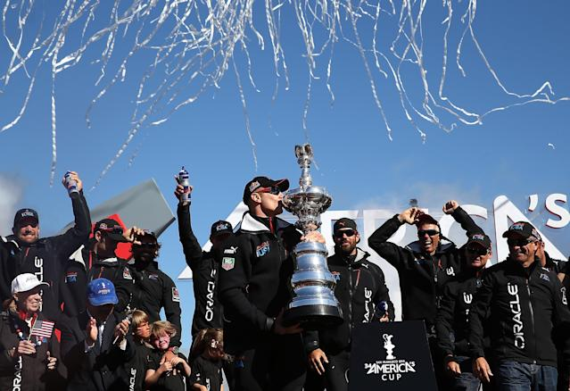 SAN FRANCISCO, CA - SEPTEMBER 25: Oracle Team USA skipper James Spithill (C) kisses the America's Cup trophy as he celebrates onstage after they beat Emirates Team New Zealand to defend the America's Cup during the final race on September 25, 2013 in San Francisco, California. (Photo by Justin Sullivan/Getty Images)