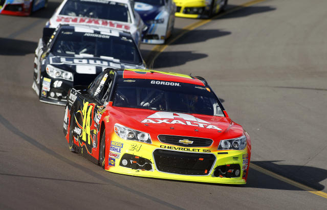 Driver Jeff Gordon (24) takes an early lead in front of points leader Jimmie Johnson (48) during the AdvoCare 500 NASCAR Sprint Cup Series auto race at Phoenix International Raceway, Sunday, Nov. 10, 2013 in Avondale, Ariz. (AP Photo/Ralph Freso)
