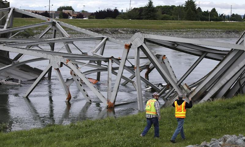 Workers walk past the collapsed portion of the Interstate 5 bridge at the Skagit River Friday, May 24, 2013, in Mount Vernon, Wash. A truck carrying an oversize load struck the four-lane bridge on the major thoroughfare between Seattle and Canada, sending a section of the span and two vehicles into the Skagit River below Thursday evening. All three occupants suffered only minor injuries. (AP Photo/Elaine Thompson)