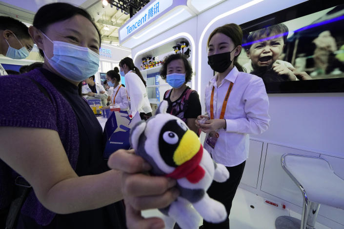 A woman holds up a soft toy at the Tencent booth during the China International Fair for Trade in Services (CIFTIS) in Beijing Monday, Sept. 6, 2021. Beijing has launched anti-monopoly and data security crackdowns to tighten control over internet giants including e-commerce platform Alibaba Group and games and social media operator Tencent Holdings Ltd. that looked too big and potentially independent. (AP Photo/Ng Han Guan)