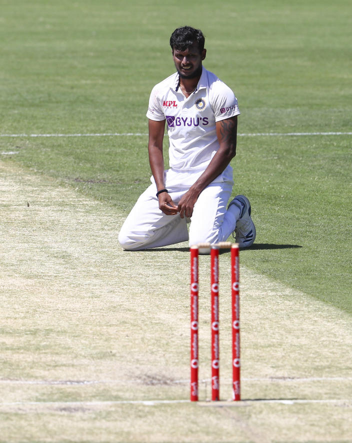 India's Thangarasu Natarajan rests on the pitch during play on day two of the fourth cricket test between India and Australia at the Gabba, Brisbane, Australia, Saturday, Jan. 16, 2021. (AP Photo/Tertius Pickard)